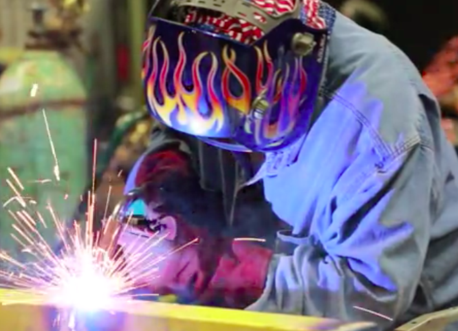 A person welding a piece of steel.